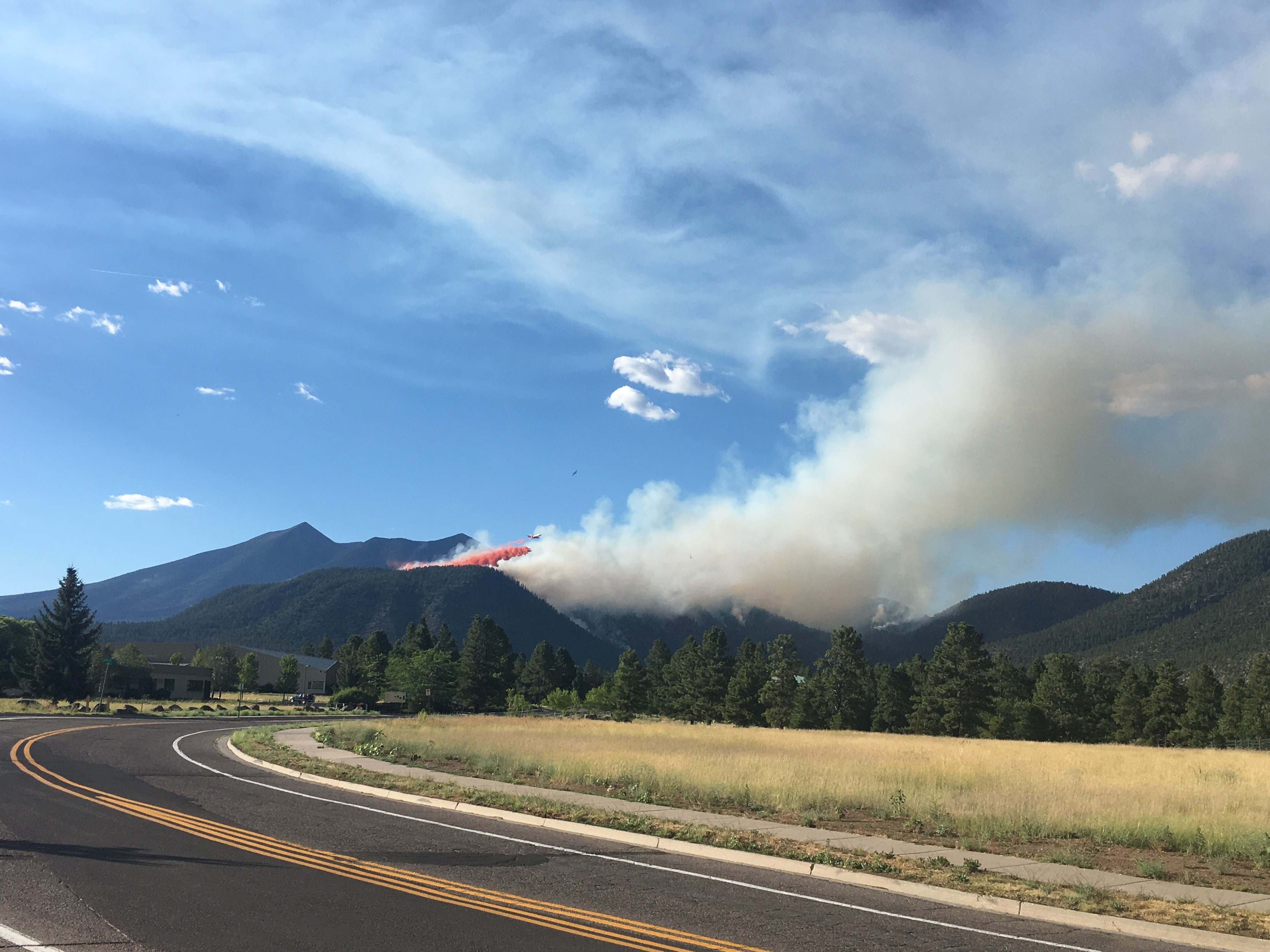 The image shows smoke related to the Museum Fire coming out of mountains in Flagstaff.
